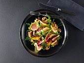 Mixed leaf salad with colourful radishes, oranges, figs, walnuts and passion fruit