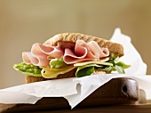 A sandwich filled with ham, cheese and lettuce