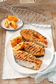 Grilled salmon steaks with orange wedges