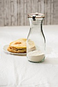 A jar containing the dry ingredient mix for making pancakes and a plate of cooked pancakes