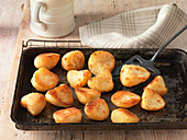 Beef dripping roast potatoes on baking tray and wire rack