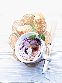 Creamy blueberry spread and a chunk of sesame bagel in a bread basket