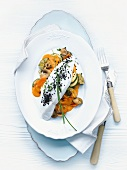 Catfish fillet with lobster butter on a bed of vegetables
