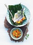 Sea bass fillet wrapped in banana leaf with mango-papaya salsa