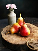 Three red and yellow pears on a wooden disc
