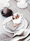 Easter place setting with feathers in cup