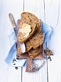 Slices of rye bread, one spread with butter, on a chopping board