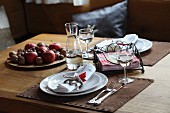 Festively set table with leather place mats and plate of fruit and nuts