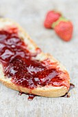 Freshly made strawberry jam on a slice of white bread