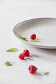 Fresh Raspberries and Mint Leaves on a White Plate