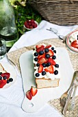 Angel food cake baked in a loaf tin and topped with fresh berries, at a picnic