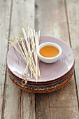Plates, a small dish of honey, and wooden skewers