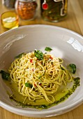 A Mediterranean pasta dish consisting of a spaghetti nest with pesto and olive oil in a deep dish