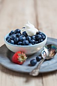 Fresh Blueberries with Whipped Cream in a Bowl; Strawberry and Spoon