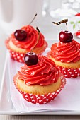 Cupcakes topped with cherry buttercream and cherries