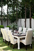 A festively laid table in a garden with white chairs