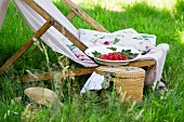 A deckchair with cushions, a straw hat and redcurrants next to a picnic basket