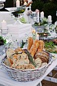 Various types of white bread in a breadbasket on a buffet table