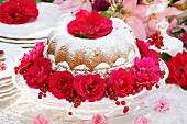Bundt cake with icing sugar, rose decorations and redcurrants