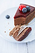 A slice of chocolate cheesecake with a raspberry and blueberries