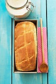 White bread in the tin, a wooden spoon, a napkin and flour