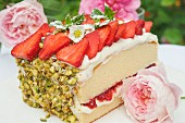A slice of sponge cake with strawberries and pistachios on a garden table