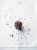 A cake pop decorated with colourful sugar balls