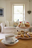 Cup of tea & pastries on cake stand on table in living room