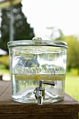 Glass container used as water dispenser on table in garden