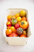 Assorted colours of tomato in a cardboard punnet