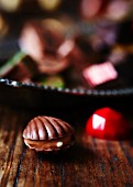 A chocolate oyster in front of assorted chocolates