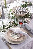 Festlich gedeckter Weihnachtstisch mit Deko in Silber, lindgrünen Kerzen und Efeuranken