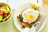 Veal schnitzel with a fried egg, lettuce and beer