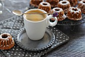 A cup of espresso with mini Bundt cakes