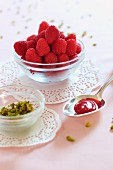 A spoon of raspberry and rose jam, chopped pistachios and fresh raspberries