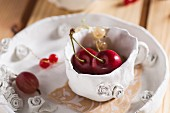 Sweet cherries, redcurrants and red gooseberries in a clay cup