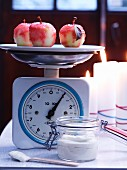 Candy apples on kitchen scales with mascarpone cream
