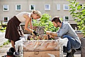 Young couple gardening on roof