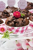 Chocolate muffins on glass cake stand decorated with flowers