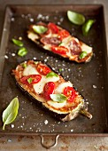 Aubergine halves topped with tomatoes and cheese and baked