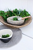 Fresh kitchen herbs with a stone mortar in a rustic wooden bowl