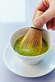 Matcha tea being stirred with a bamboo whisk