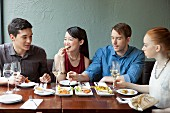 Four friends eating food in restaurant