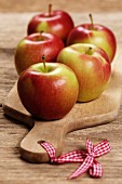 Several Braeburn apples on a chopping board