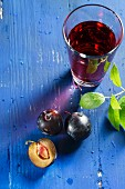 Plums and plum juice on a blue tabletop