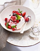 Bowl of pavlova with cranberries and raspberries