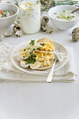 A bread roll topped with scrambled egg and served with baked radish