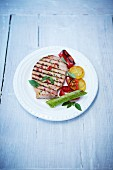 Grilled smoked pork chop with peppers and lemon