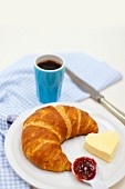 Croissant with jam and a heart-shaped pat of butter, and a cup of coffee