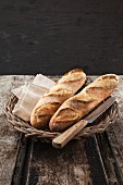 Baguettes in a basket with a knife